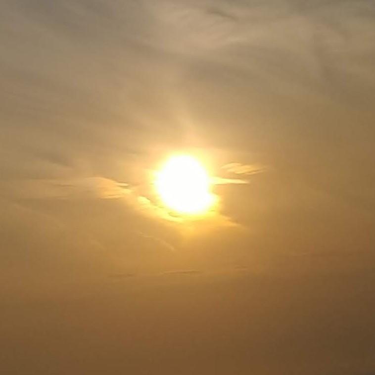 夕陽。太陽の近くの雲が照らされている